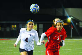 Edwardsville's Emma Sitton, left, chases down a loose ball against Incarnate Word's Maggie O'Brien in the second half.