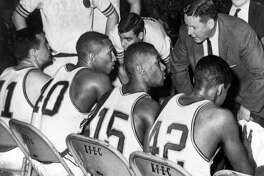 In this March 23, 1963, file photo, Loyola coach George Ireland, right, bends over to issue orders to his team that was trailing Cincinnati in the final game of the National Collegiate basketball championship at Louisville, Ky. Players, from left to right, are: John Egan, Vic Rouse, Jerry Harkness and Ron Miller. The Ramblers play Nevada on Thursday, March 22, 2018, after two thrilling wins to reach the Sweet 16, earning more wins this season than the team that won the 1963 title. (AP Photo/File)