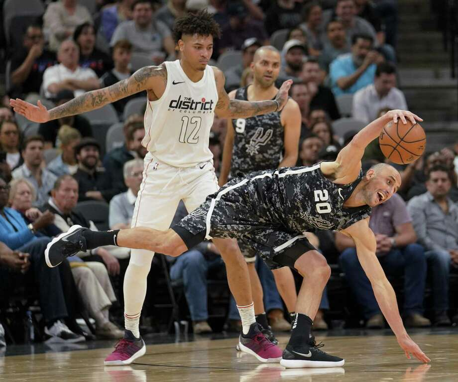 San Antonio Spurs' Manu Ginobili (20) fights for possession against Washington Wizards' Kelly Oubre Jr. during the first half of an NBA basketball game Wednesday, March 21, 2018, in San Antonio. Photo: Darren Abate /Associated Press / FR115 AP