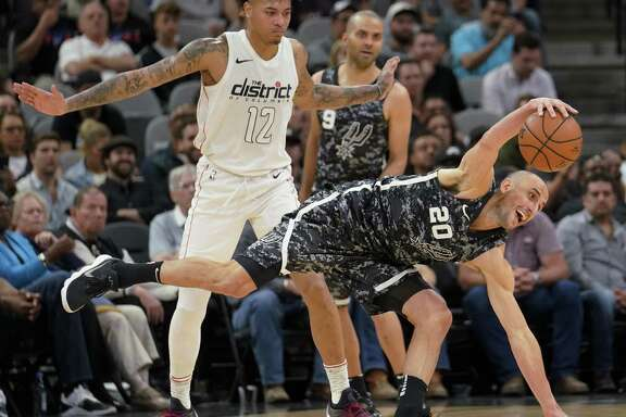 San Antonio Spurs' Manu Ginobili (20) fights for possession against Washington Wizards' Kelly Oubre Jr. during the first half of an NBA basketball game Wednesday, March 21, 2018, in San Antonio.