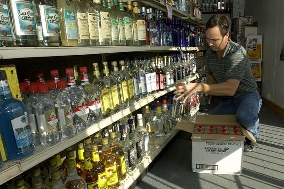"Greg Tannery stocks shelves in his liquor store, 105 Package Store, Friday, Nov. 14, 2003, in Conroe, Texas. A petition drive is being circulated to make the south side of 105, currently a dry precint in Montgomery County, wet as well.  Tannery's store sits on the ""wet"" side of 105."