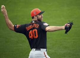 FILE - In this Feb. 15, 2018 file photo, San Francisco Giants' Madison Bumgarner throws during a spring training baseball practice in Scottsdale, Ariz. Bumgarner learned a tough lesson and he's ready for a do-over. San Francisco's ace is as motivated as ever after the embarrassment of a dirt bike accident that cost him nearly three months and contributed to his club falling out of contention in a hurry. Same goes for all of the Giants, fueled by an uncharacteristic 98-loss, last-place season. (AP Photo/Ben Margot, File)
