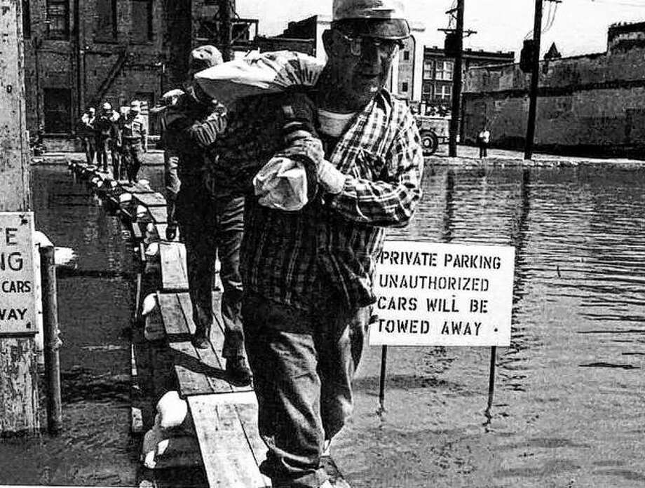 The year 1973 not only brought the worst flooding known to the Mississippi Valley, it brought more than one flood. The first flood was in April of that year. Volunteers walk a sandbagged bridge across the rising floodwaters in downtown Alton. Photo: File Photo