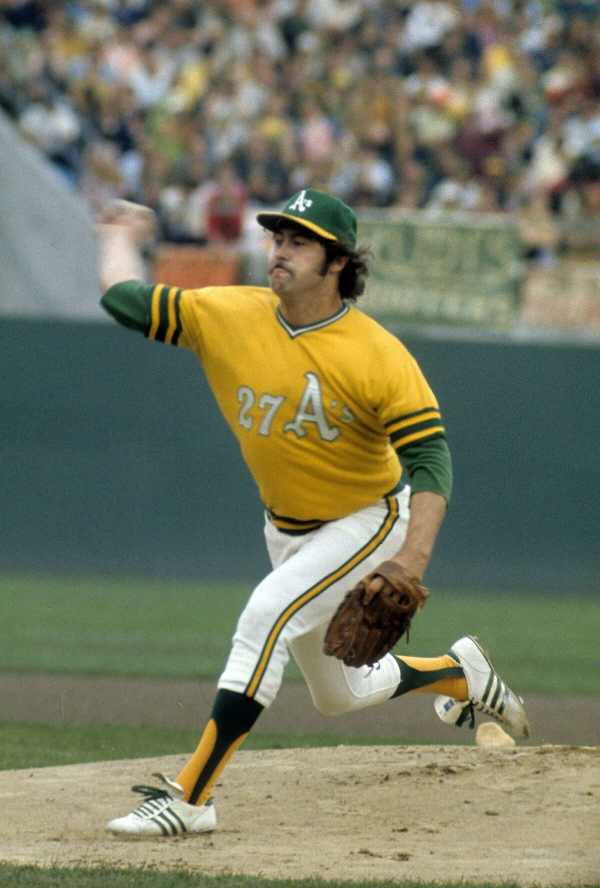 OAKLAND, CA - CIRCA 1970's: Pitcher Jim Catfish Hunter #27 of the Oakland Athletics pitches during a circa early 1970's Major League baseball game at the Oakland Coliseum in Oakland, California. Hunter played for the Athletics from 1965-74. (Photo by Focus on Sport/Getty Images)