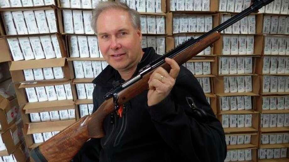 Randy Brown, of Randy's Hunting Center in Bad Axe, shows the engraved Ruger 'Scout' Rifle in .450 Bushmaster that he received for his family firearms business being named the 2017 Ruger Retailer of the Year. Behind him are boxes of the Ruger American Ranch rifle in .450 Bushmaster that has become a very popular deer rifle for southern Michigan. (Tom Lounsbury/Hearst Michigan)