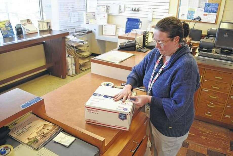Sarah Williamson, officer in charge of the Virginia Post Office, gets a Priority Mail box ready for a customer Wednesday at the post office. Photo: Greg Olson | Journal-Courier