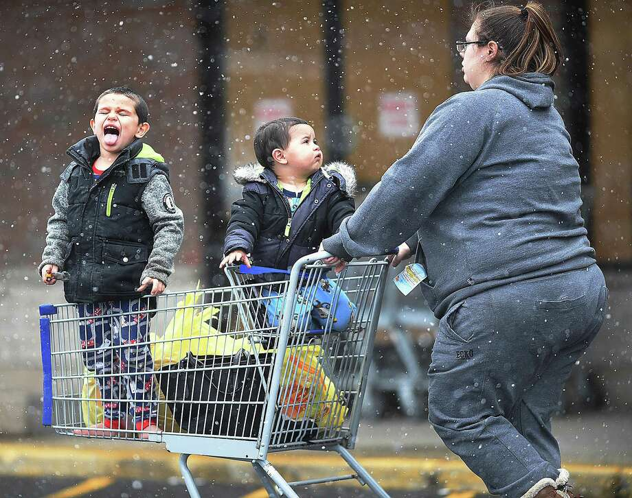 A young boy catches snowflakes on his tongue while riding in a shopping cart during light snowWednesday at Shop Rite in East Haven. Photo: Catherine Avalone / Hearst Connecticut Media / New Haven Register