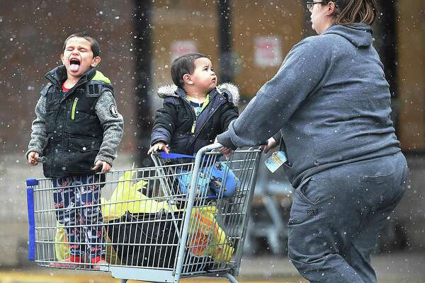 A young boy catches snowflakes on his tongue while riding in a shopping cart during light snowWednesday at Shop Rite in East Haven.