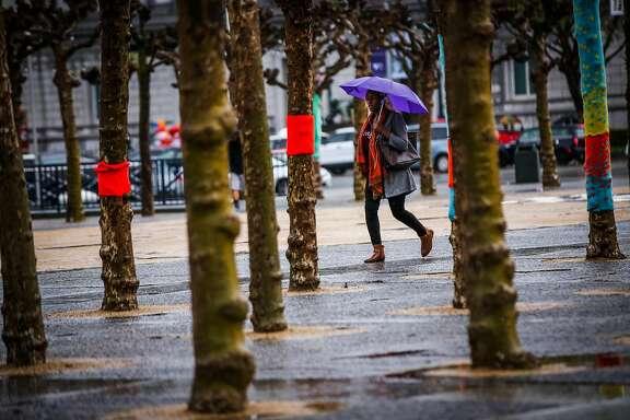 A woman walks near Civic Center in the rain in San Francisco, California, on Tuesday, March 13, 2018.