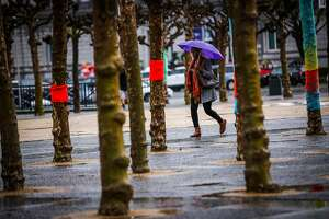 A woman walks near Civic Center in the rain in San Francisco, California, on Tuesday, March 13, 2018.