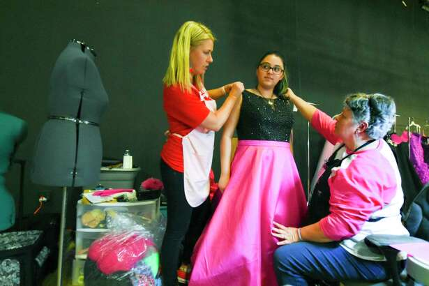Giving Gown Foundation volunteer Kristin Kirch helps Westfield High School student Stephanie Galuan with her prom dress fitting along with Danielle La Pell at the Bammel Church of Christ.