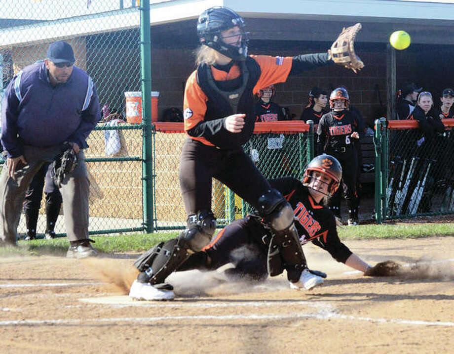 Edwardsville's Anna Burke (bottom) slides in safely to home plate while Gillespie catcher Mackenzie Kasarda takes the throw during the first inning Wednesday at the District 7 Sports Complex in Edwardsville. Photo: Matthew Kamp / For The Telegraph