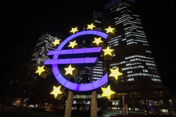 The euro sign sculpture stands illuminated near the former European Central Bank (ECB) headquarters at night in Frankfurt, Germany, on Nov. 6, 2017.