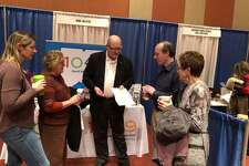 Middletown's WIHS-FM Christian radio station is marking 50 years in business. Announcer Jack Pike, center, talks with attendees of the GO Conference in Springfield, Massachusetts.