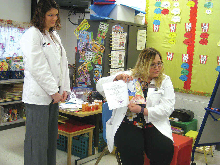 "SIUE pharmacy student Sarah Rhone, standing, listens as fellow student Erin Ball reads ""Sarah's Sick Day"" to students at Midway Elementary School. Photo: Julia Biggs • Jbiggs.edwi@gmail.com"