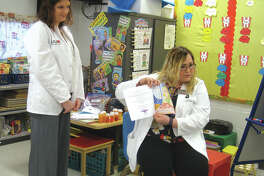 "SIUE pharmacy student Sarah Rhone, standing, listens as fellow student Erin Ball reads ""Sarah's Sick Day"" to students at Midway Elementary School."