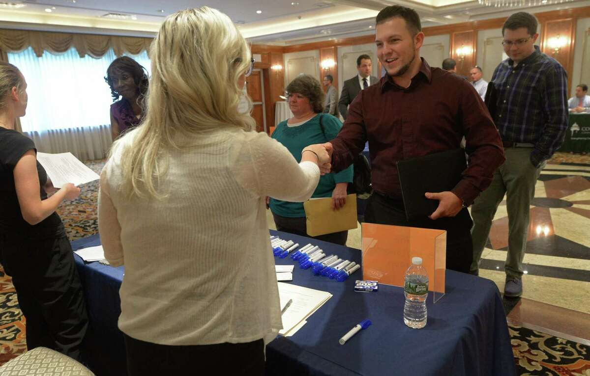 Juliet Gallicano, director of accounting and finance with The Execusearch Group, greets Ryan McNamara during the Fairfield County Job Fair at the Norwalk Inn and Conference Center on Sept. 14, 2017, in Norwalk, Conn.