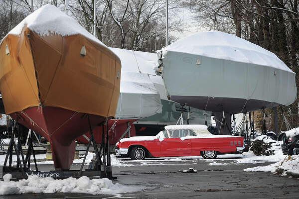 Boats and a classic car are covered in a coating of snow at Milford Boat Works marina in Milford, Conn. on Thursday, March 22, 2018.