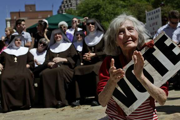 Applauding a speaker, Tessye Maurer sits in front of a group of Poor Clare Nuns of Perpetual Adoration during the Stand Up for Religious Freedom Rally in 2012. When the same picture was republished recently, she wondered if a higher voice was reaching out to her.