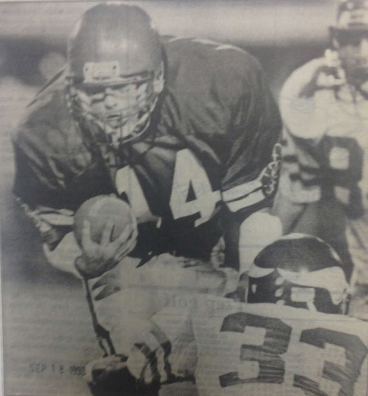 Midland High's Rod Bauer (14) powers his way through the Flint Northern defensive line at Midland Stadium on Friday night, Sept. 17, 1993. Midland won 23-6.