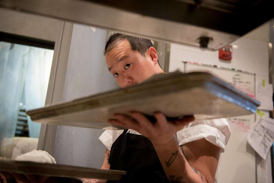Eric Ehler carries trays of salted trout at Mister Jiu's. Photo: Rosa Furneaux, Special To The Chronicle