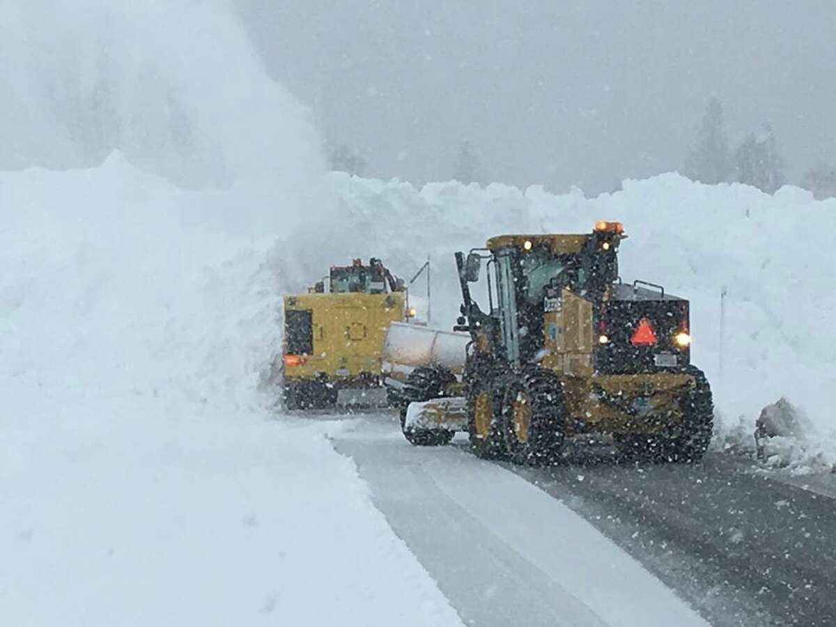 """Snow ploughs remove heavy snow piled up on State Route 88 in Amador County over the Carson Spur as a moisture-rich """"atmospheric river"""" slams the Sierra Nevada."""