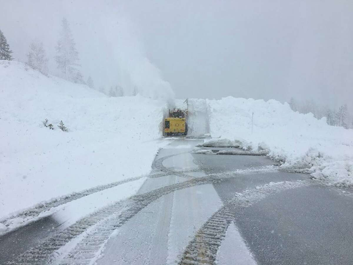 Snow ploughs remove heavy snow piled up on State Route 88 in Amador County over the Carson Spur as a moisture-rich