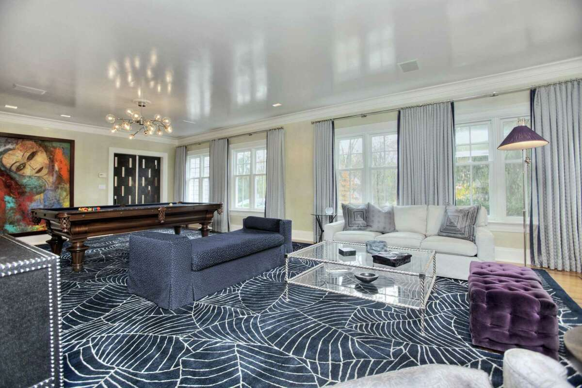 The spacious formal living room has Venetian waxed walls and ceiling with art lights and includes a sitting area and a billiard area.