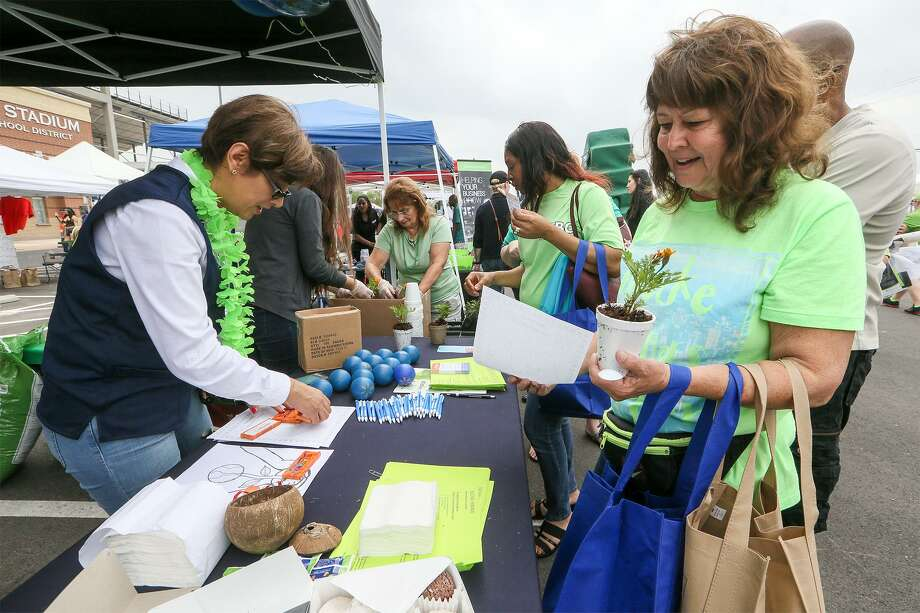 Teresa Morrison (right) receives a plant and information on planting and recycling from Angelica Iltis  at the Walmart booth. Photo: Marvin Pfeiffer /San Antonio Express-News / Express-News 2018