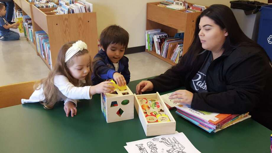 Converse resident Crystal Cantu, right, watches as Savannah Acosta, 2, and Miguel Angel Pacheco, 3, play at a table in the newly expanded Converse Public Library. Photo: Jeff B. Flinn / NE Herald / Jeff B. Flinn / NE Herald