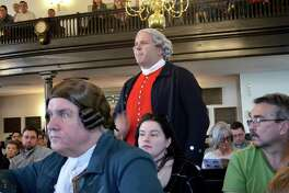 In a reenactment of the Second Virginia Convention, Mike Carioscia, center, as Benjamin Harrison, objects to the resolution by Patrick Henry, portrayed by John Tucker, left.