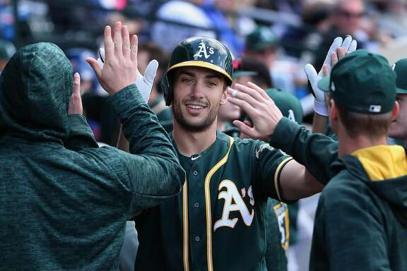 MESA, AZ - FEBRUARY 28:  Matt Olson #28 of the Oakland Athletics high fives teammates in the duggout after hitting a solo home run against the Chicago Cubs during the fourth inning of the spring training game at Sloan Park on February 28, 2018 in Mesa, Arizona.  (Photo by Christian Petersen/Getty Images)