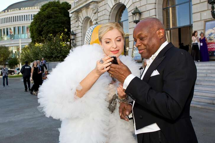 Sonya Molodetskaya looks over cell phone photos taken by a friend with former San Francisco Mayor Willie Brown after arriving at the San Francisco Opera Opening Night Gala at War Memorial Opera House in San Francisco, Calf., on Friday, September 7, 2012.