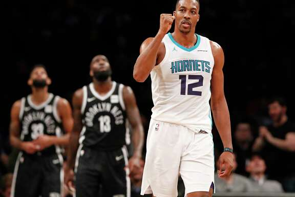 Charlotte Hornets center Dwight Howard (12) reacts during the second half of the team's NBA basketball game against the Brooklyn Nets on Wednesday, March 21, 2018, in New York. Brooklyn Nets guard Allen Crabbe (33) and forward Quincy Acy (13) watch a video replay. The Hornets won 111-105. (AP Photo/Kathy Willens)