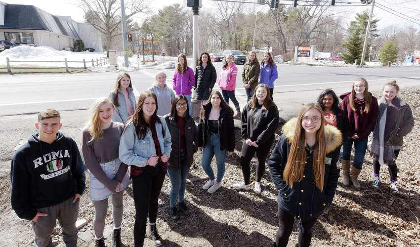 Mohonasen High School students pose across the street from the school entrance on Thursday, March 22, 2018, in Rotterdam, N.Y. Anna Sherman, foreground right, raised enough money through GoFundMe to charter a bus to take her and over 30 of her fellow students to Washington D.C. for the march this Saturday. (Paul Buckowski/Times Union)