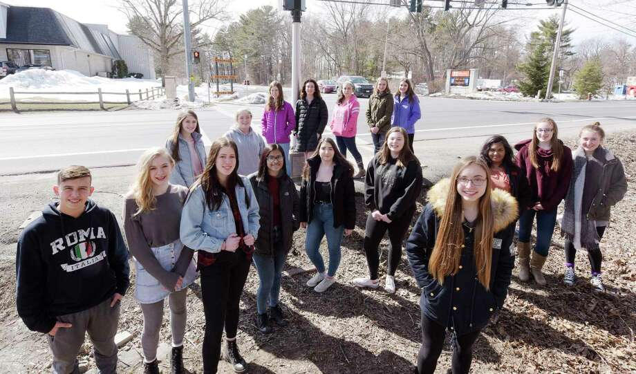 Mohonasen High School students pose across the street from the school entrance on Thursday, March 22, 2018, in Rotterdam, N.Y. Anna Sherman, foreground right, raised enough money through GoFundMe to charter a bus to take her and over 30 of her fellow students to Washington D.C. for the march this Saturday.   (Paul Buckowski/Times Union) Photo: PAUL BUCKOWSKI, Albany Times Union / (Paul Buckowski/Times Union)