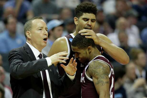 CHARLOTTE, NC - MARCH 18: Head coach Billy Kennedy, Tyler Davis #34, and TJ Starks #2 of the Texas A&M Aggies react after defeating the North Carolina Tar Heels 86-65 during the second round of the 2018 NCAA Men's Basketball Tournament at Spectrum Center on March 18, 2018 in Charlotte, North Carolina.