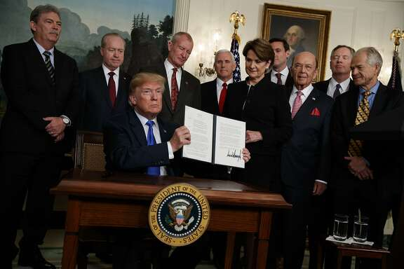 President Donald Trump shows off a signed Presidential Memorandum imposing tariffs and investment restrictions on China, in the Diplomatic Reception Room of the White House, Thursday, March 22, 2018, in Washington. (AP Photo/Evan Vucci)