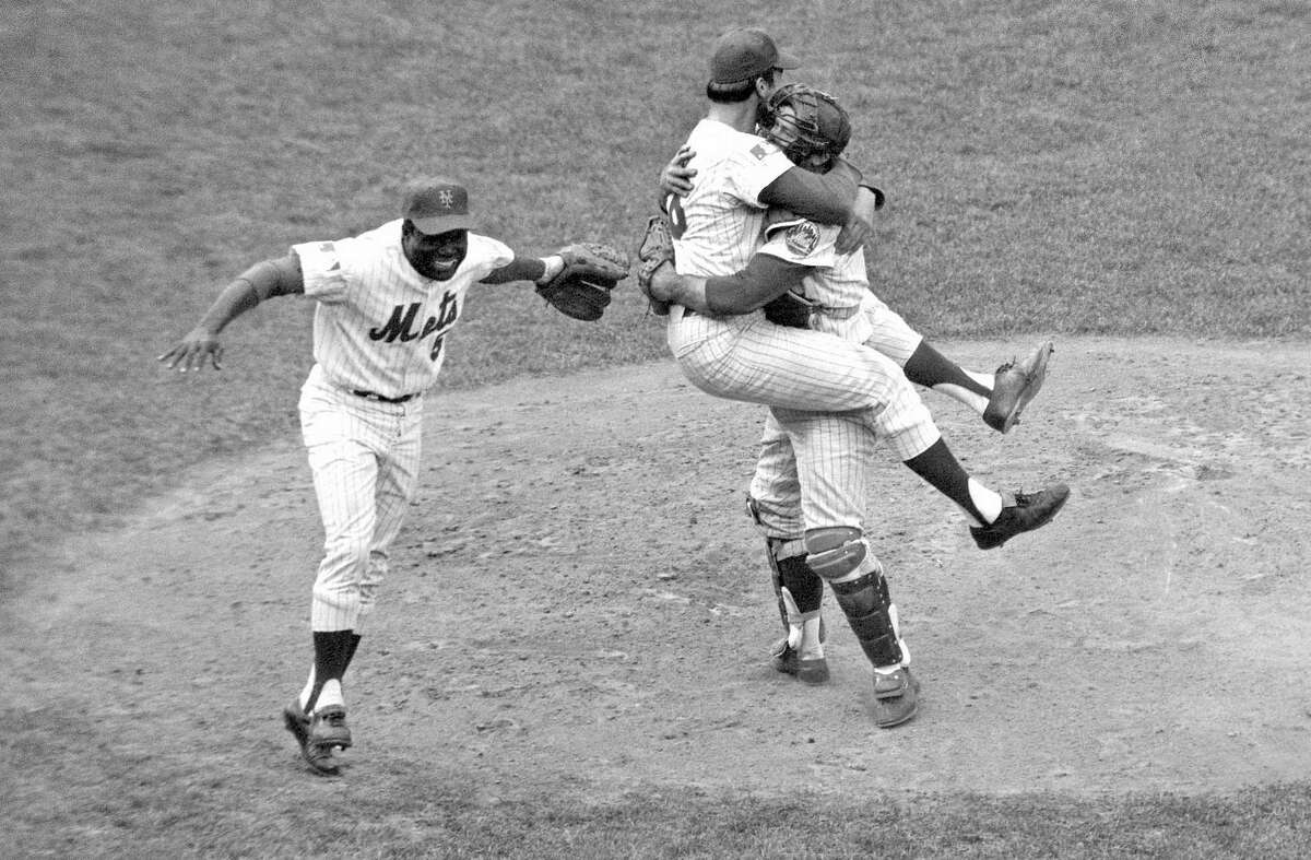 New York Mets catcher Jerry Grote embraces pitcher Jerry Koosman as Ed Charles, left, joins the celebration after the Mets defeated the Baltimore Orioles in the Game 5 to win baseball's World Series at Shea Stadium on Oct. 16, 1969.