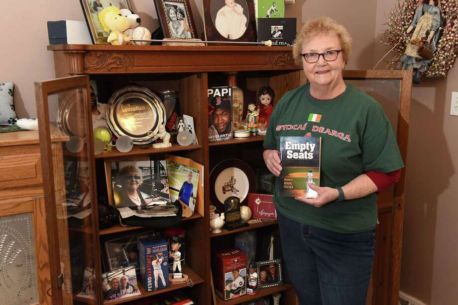 "Wanda Fischer stands next to her baseball paraphernalia at her home on Friday, March 16, 2018 in Schenectady, N.Y. She's holding a copy of the book she wrote titled ""Empty Seats."" (Lori Van Buren/Times Union) Photo: Lori Van Buren / 20043239A"