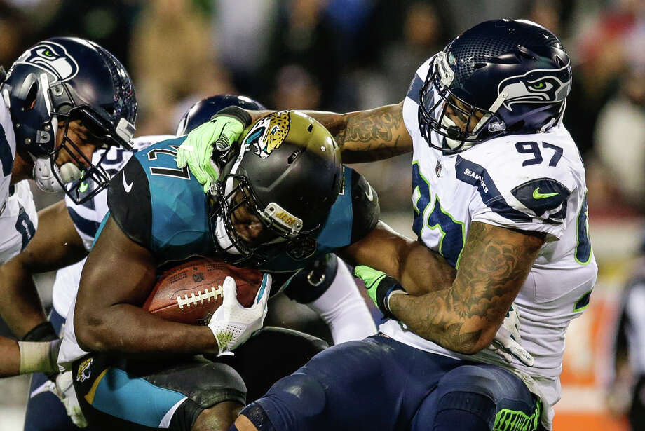 JACKSONVILLE, FL - DECEMBER 10:  Seattle Seahawks defensive end Marcus Smith (97) tackles Jacksonville Jaguars running back Leonard Fournette (27) during the game between the Seattle Seahawks and the Jacksonville Jaguars on December 10, 2017 at EverBank Field in Jacksonville, Fl. (Photo by David Rosenblum/Icon Sportswire via Getty Images) Photo: Icon Sportswire/Icon Sportswire Via Getty Images