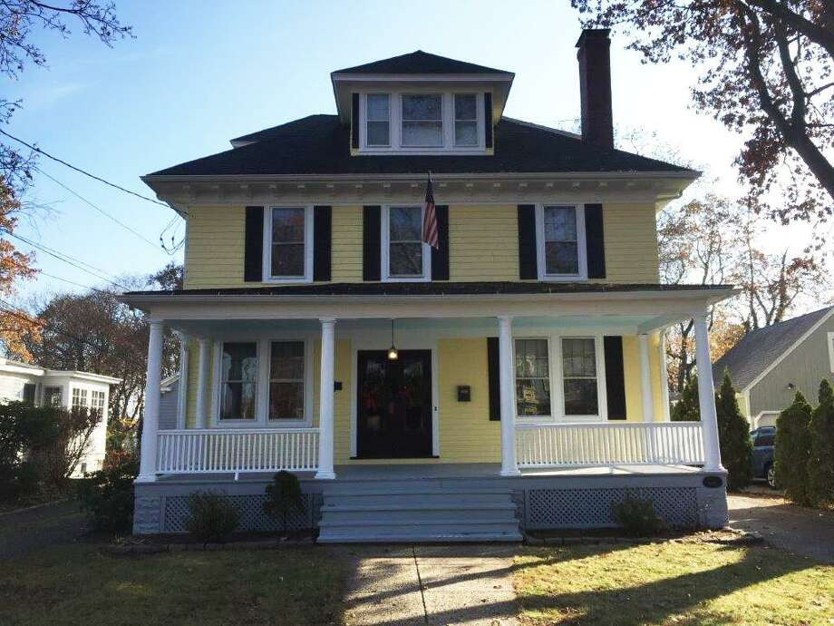 The classic Foursquare-style house at 27 Green St. in Milford was built in the early 20th century by Alfred Gould, of Milford's Harrison and Gould's Hardware store. The 2,938-square-foot, six-bedroom house reflects Gould's love of hardware and handicraft, with touches that include an iron spot brick fireplace, and red oak columns in many of the doorways. Photo: Contributed / Contributed