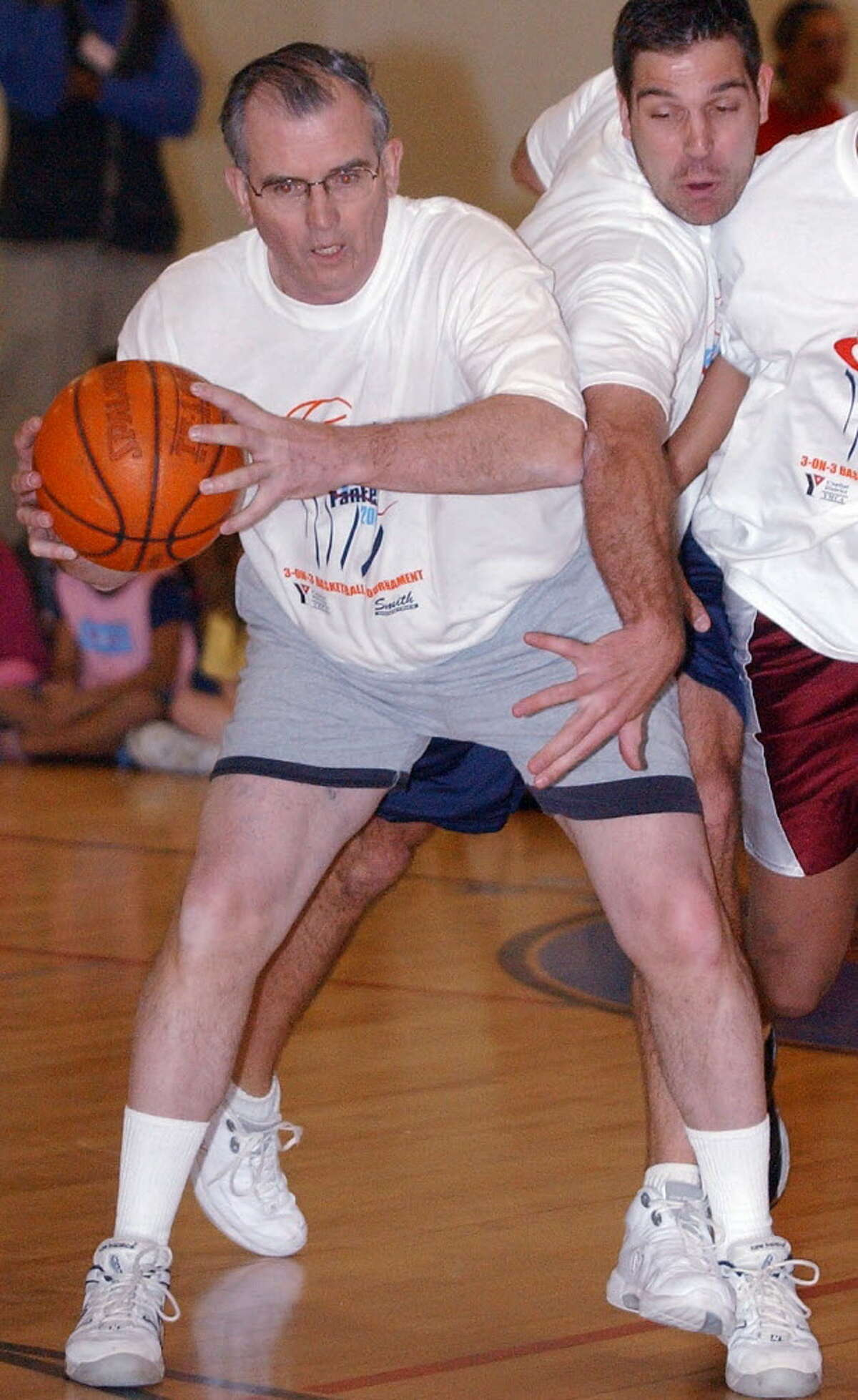 Albany County Executive Mike Breslin handles the ball as Greg Koubek defends during the 3-on-3 basketball game opening a 3-on-3 basketball tournament in conjunction with the NCAA East Regional at the Pepsi Arena on Feb. 18, 2003.
