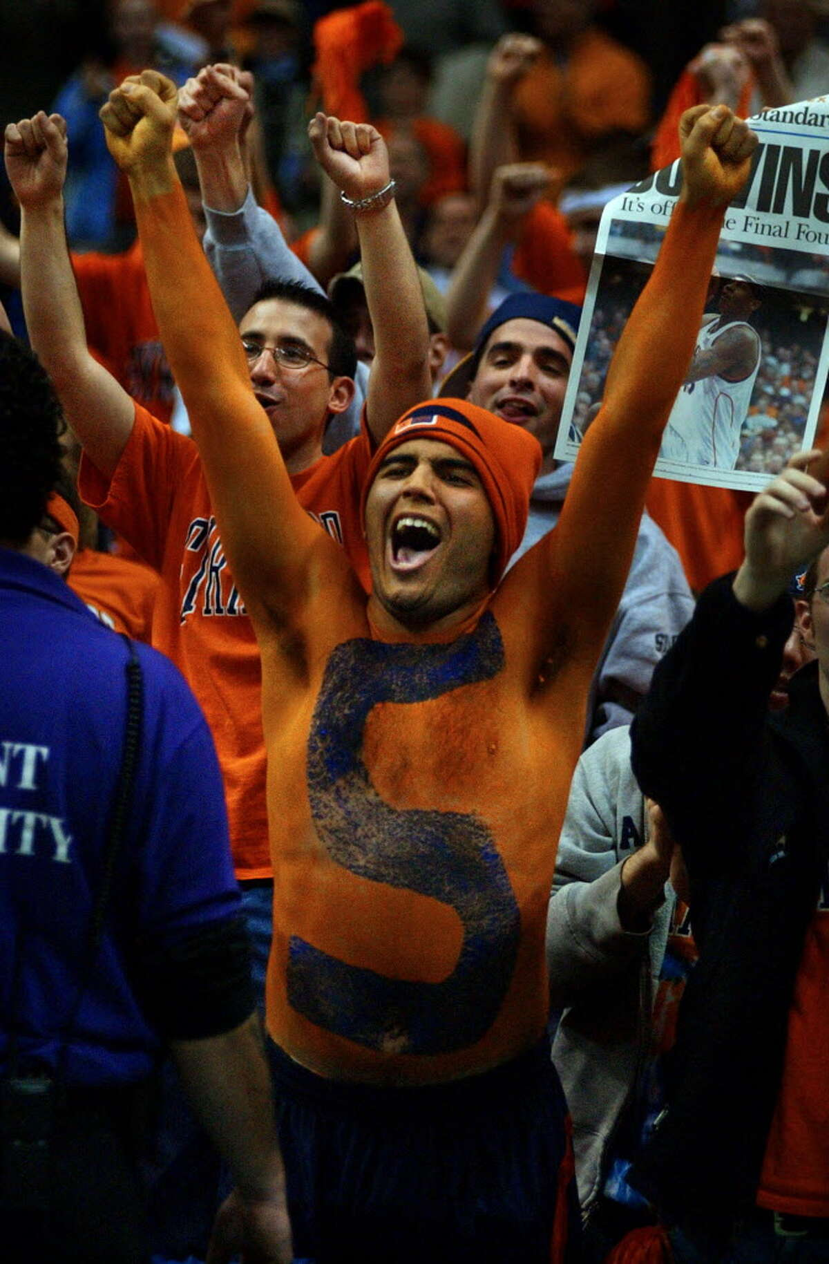 Times Union Staff photograph by Philip Kamrass -- Syracuse University freshman Nick Friedell of Orlando, Florida sports orange and blue body paint while celebrating after his team's 63-47 victory over Oklahoma in the NCAA East Regional at the Pepsi Arena in Albany, NY Sunday March 30, 2003. A copy of the Syracuse Post Standard front page reporting the win is in the background at right.
