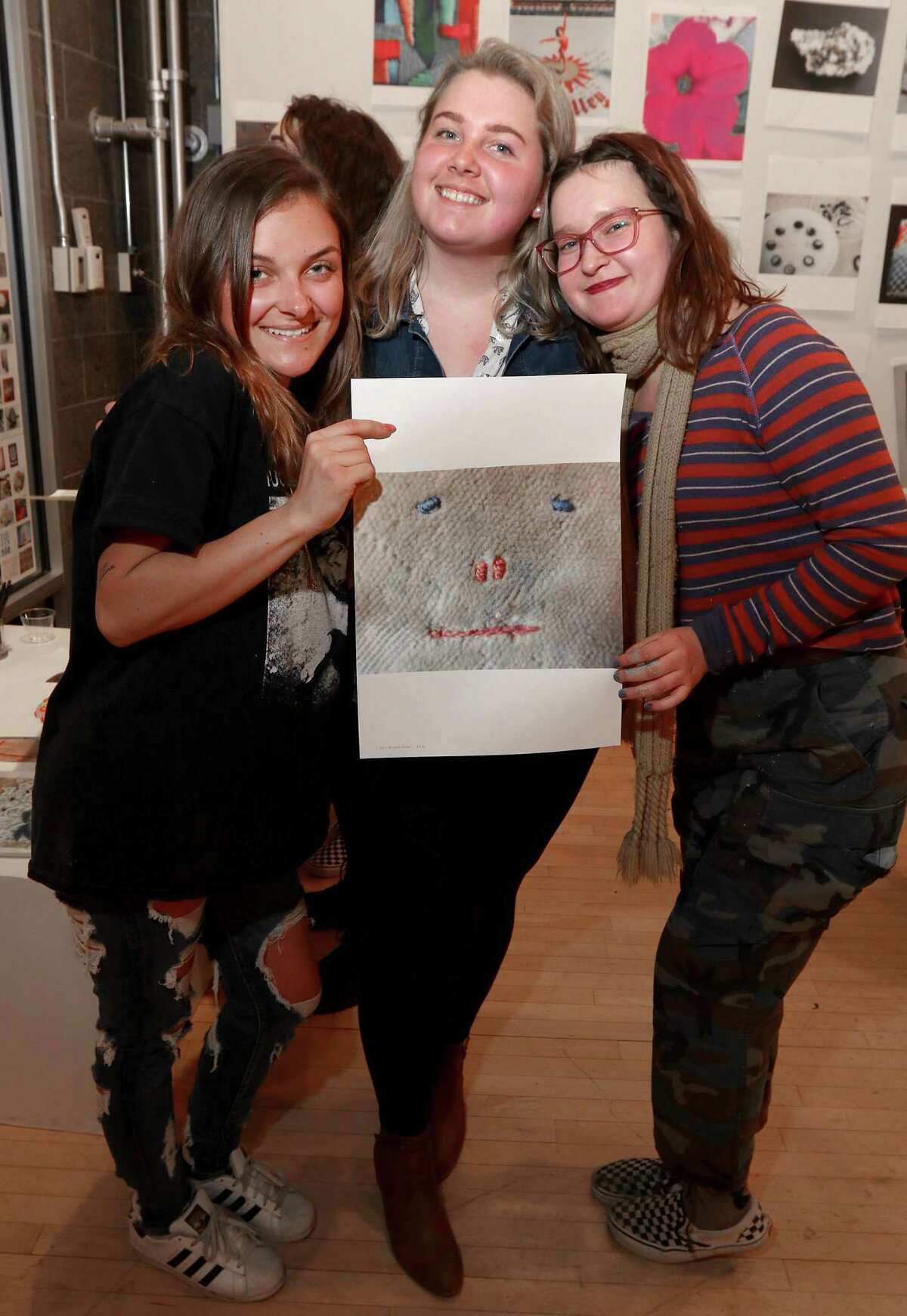 Albany, NY - March 16, 2018 - (Photo by Joe Putrock/Special to the Times Union) - (l to r) Victoria Stockman, Madison Scisci and Lea Diep hold a piece of work by exhibiting photographer Polly Apfelbaum during The 40th Annual Photo Regional: Effects That Aren?'t Special opening reception at the Opalka Gallery on the Sage College of Albany campus.