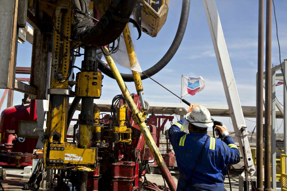 A Nabors Industries Ltd. roughneck uses a power washer to clean the drilling floor of a rig drilling for Chevron Corp. in the Permian Basin near Midland, Texas, U.S., on Thursday, March 1, 2018. Chevron, the world's third-largest publicly traded oil producer, is spending $3.3 billion this year in the Permian and an additional $1 billion in other shale basins. Its expansion will further bolster U.S. oil output, which already exceeds 10 million barrels a day, surpassing the record set in 1970. Photographer: Daniel Acker/Bloomberg Photo: Daniel Acker/Bloomberg