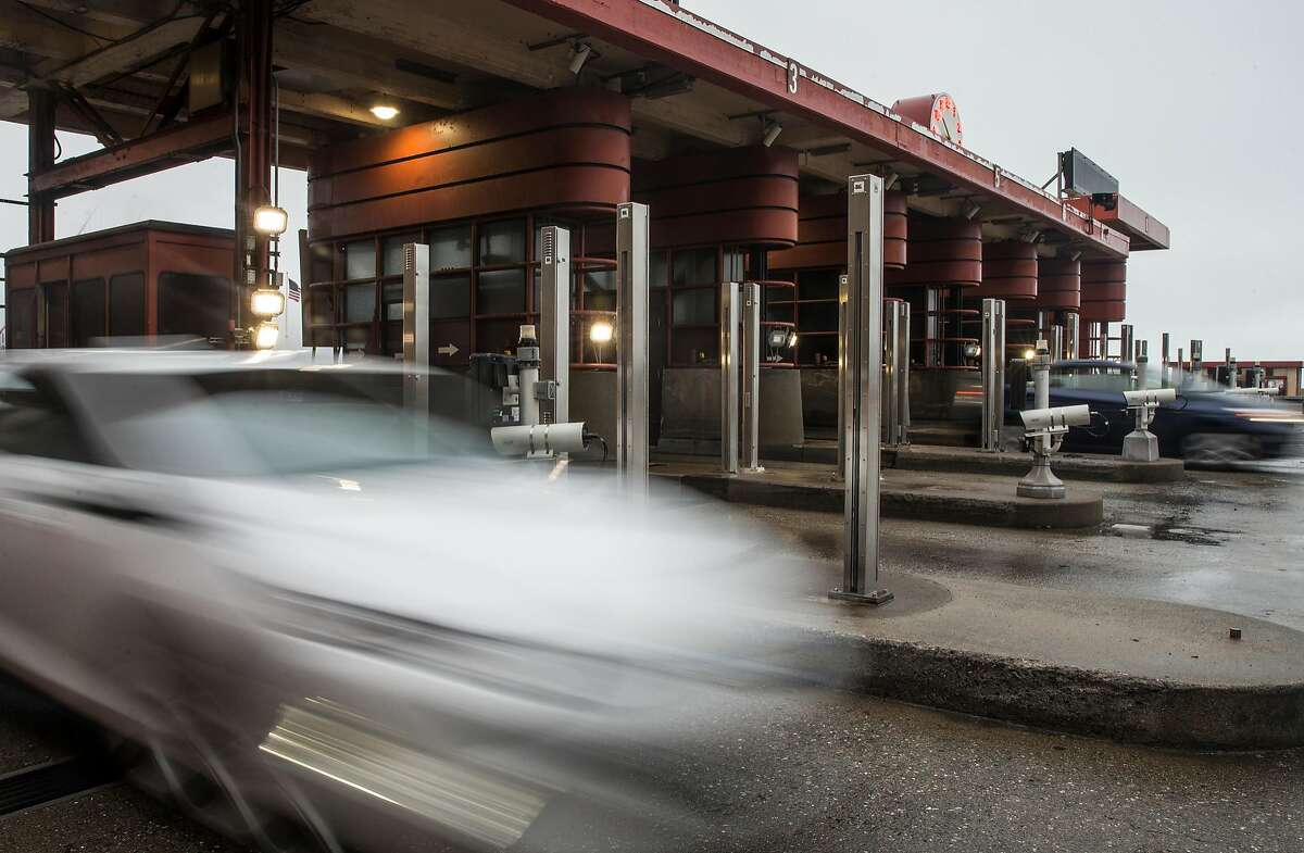 Cars move through the Golden Gate Bridge Toll Plaza during a rainy morning commute Thursday, March 22, 2018 in San Francisco, Calif.