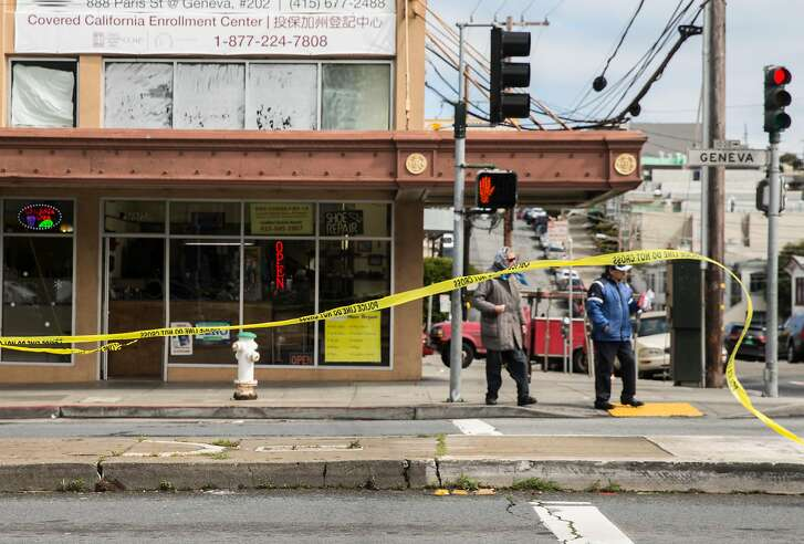 Crime scene tape whips in the wind as pedestrians cross Geneva Avenue Thursday, March 22, 2018 in San Francisco, Calif. following a shooting that occurred nearby at Amazon Barber Shop Wednesday, March 21.