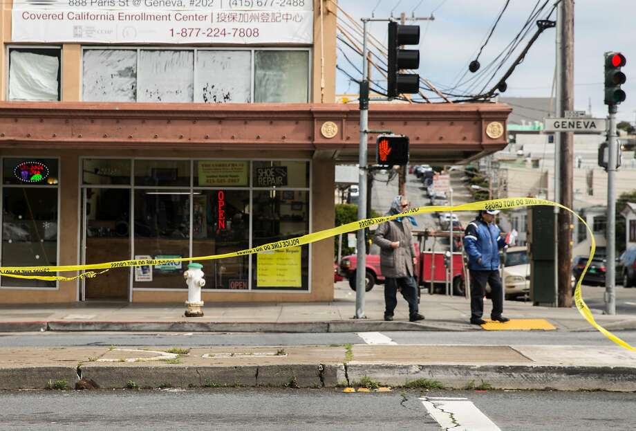 Crime scene tape whips in the wind as pedestrians cross Geneva Avenue Thursday, March 22, 2018 in San Francisco, Calif. following a shooting that occurred nearby at Amazon Barber Shop Wednesday, March 21. Photo: Jessica Christian / The Chronicle