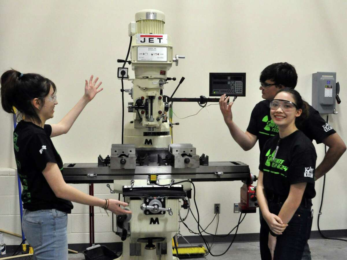 Cinco Ranch High School students Bella Riffle, Bailey Egan and Kyna McGill look at a high-tech milling machine bought by the Katy Independent School District to support robotics teams entered in international competitions. The Cinco Ranch students are among 99 teens who joinedFIRST Robotics Team 624, known as CRyptonite.